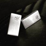 Grawerowanie laserowe inicjałów na srebrnych spinkach do mankietów firmy Lambert